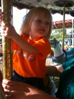 Kaitlyn riding the merry-go-round at the fair